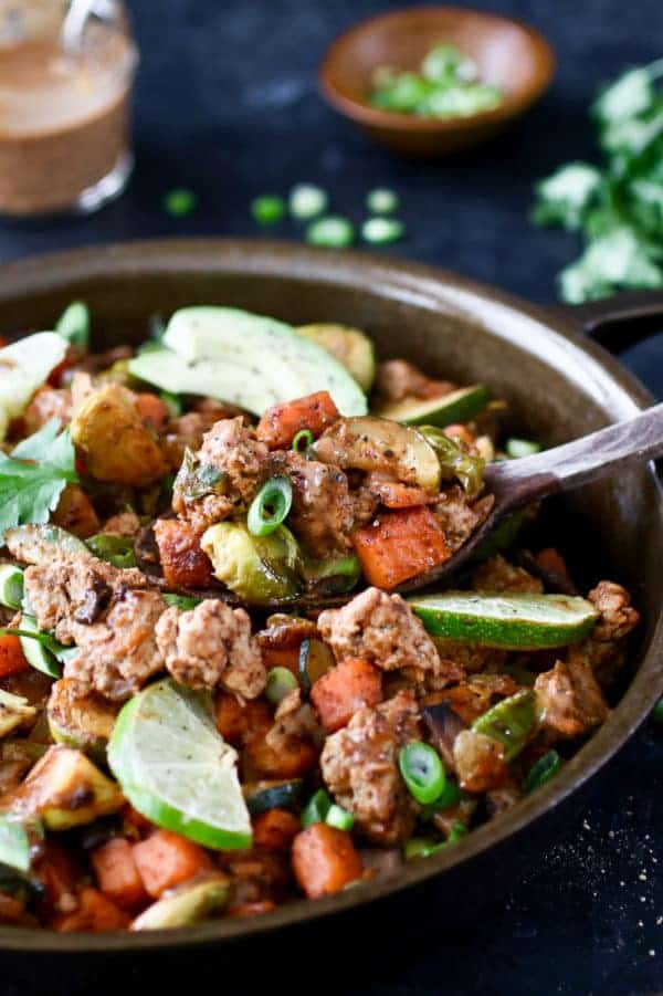 Photo of BBQ Ranch Turkey Veggie Skillet in a cast-iron topped with lime wedges, avocado, cilantro and green onion.