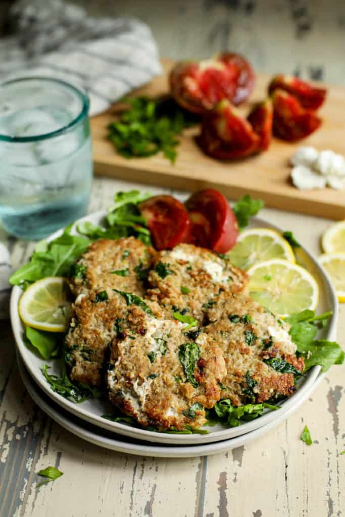 Turkey burgers on plate garnished with tomatoes and citrus over a bed of greens served with a glass of ice water. Cutting board in background with tomatoes and fresh herbs.