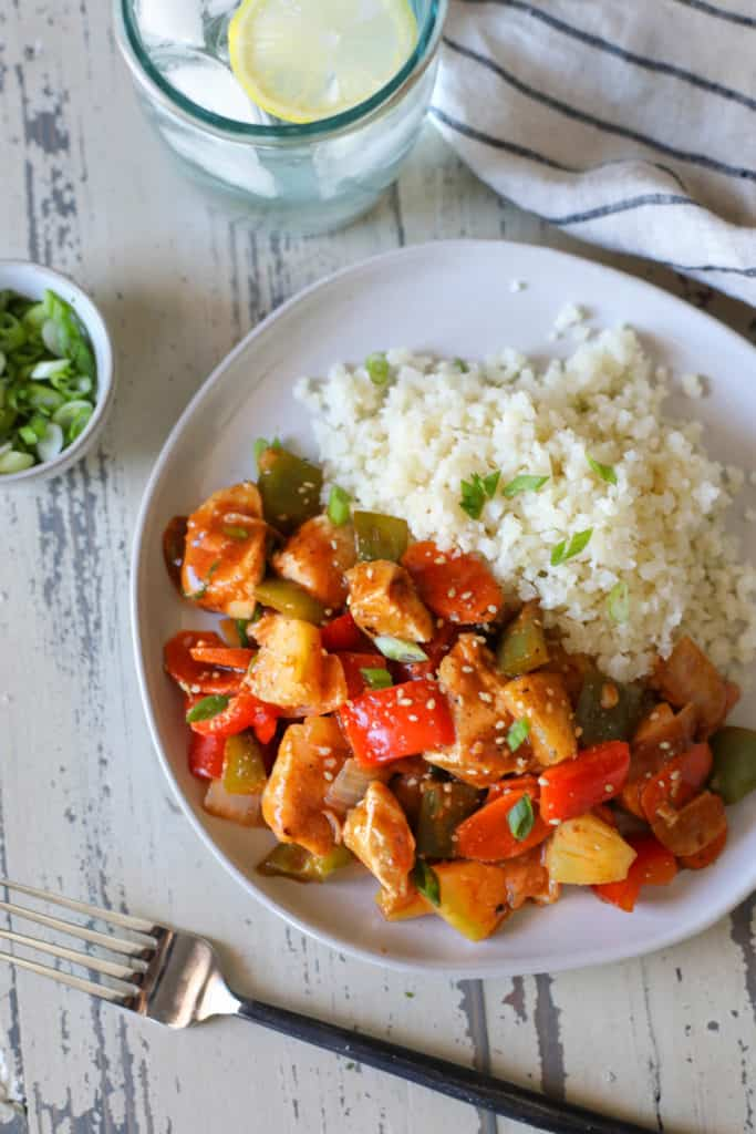 Sweet and Sour chicken with peppers and a side of cauliflower rice on white distressed background with a bowl of green onions and glass of lemon water. 4 of 10 Quick and Easy Dinner Ideas.