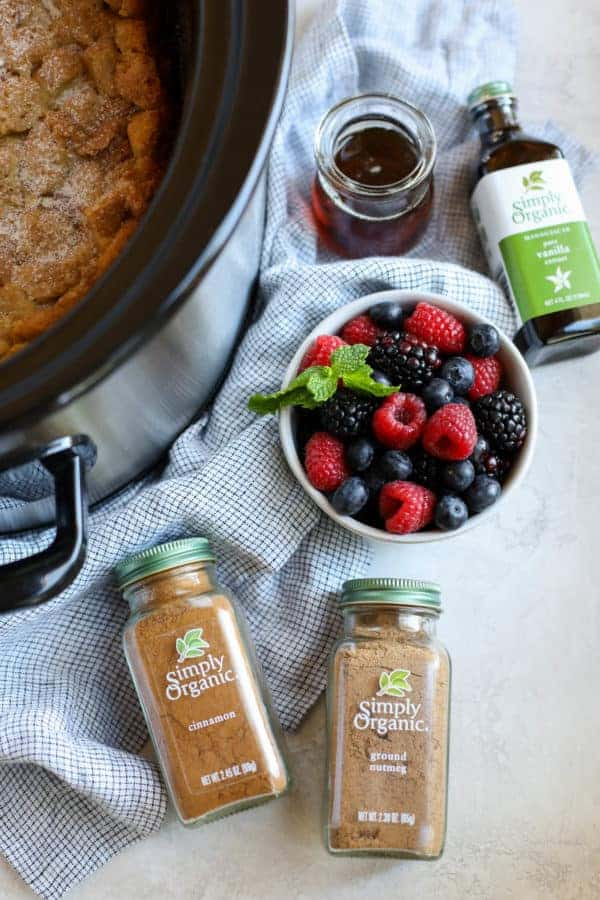 Overhead photo of ingredients for the french toast casserole include a bowl of berries, maple syrup, Simply Organic Cinnamon, Simply Organic Nutmeg and Simply Organic Vanilla Extract