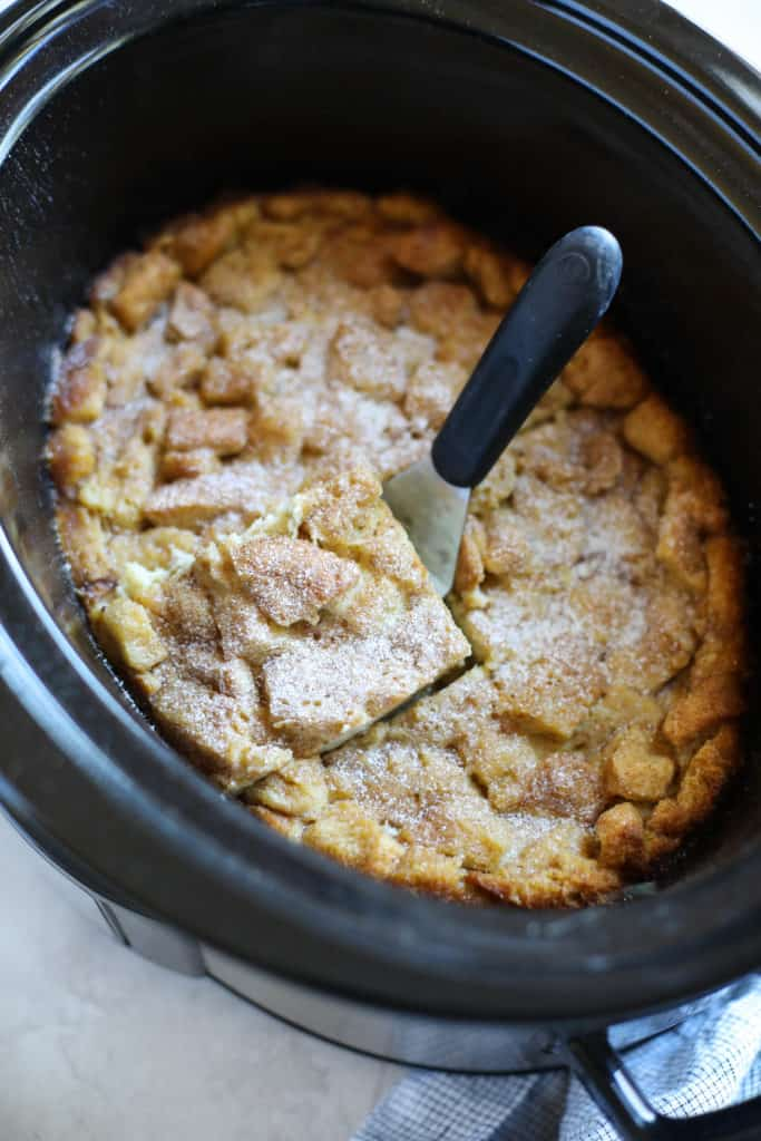 Slow cooker with French Toast Casserole with a piece cut and spatula ready to dish out
