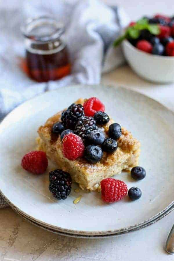 A piece of French Toast Casserole with berries on a white plate surrounded by a cup of coffee, bowl of berries and small glass of maple syrup