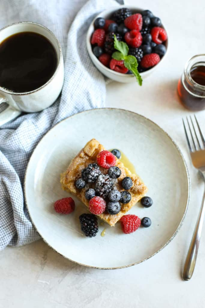 A piece of French Toast Casserole with berries on a white plate surrounded by a cup of coffee, bowl of berries and small glass of maple syrup and fork