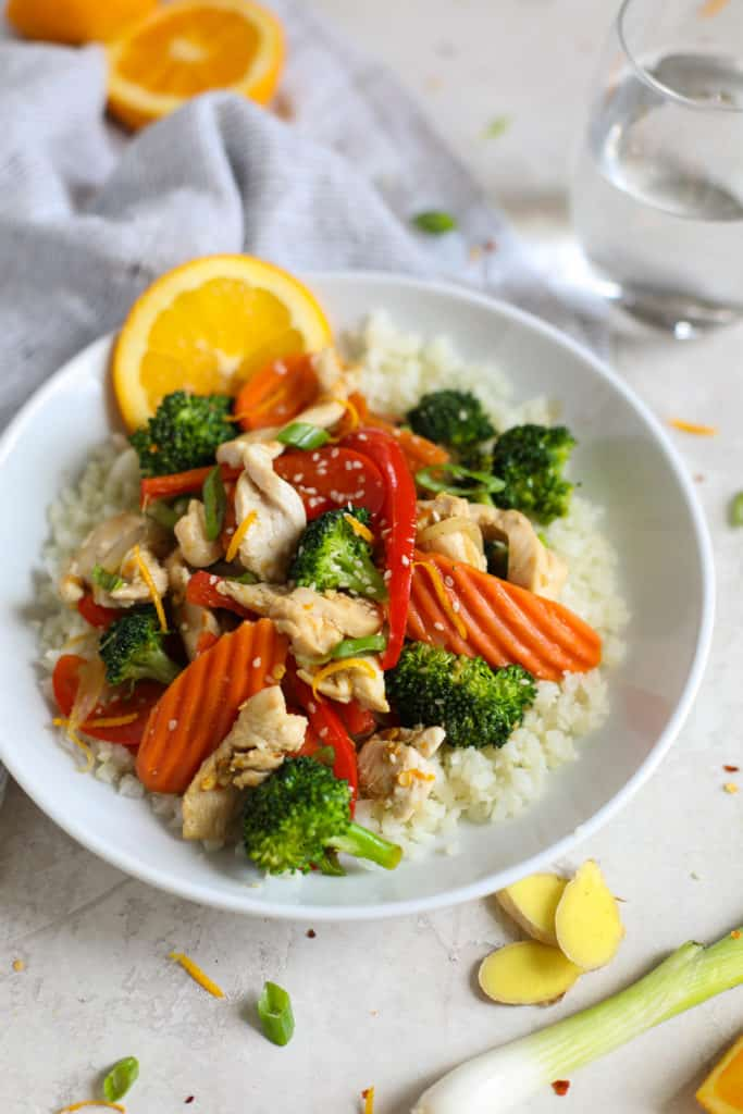 White plate with stir fry chicken with carrots, broccoli, cauliflower rice and an orange garnish with a glass of water.