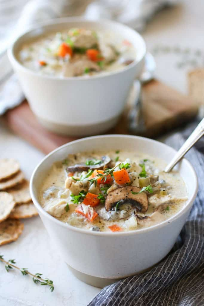 Overhead picture of Slow Cooker Creamy Chicken Wild Rice Soup. Topped with a mixture of fresh thyme, veggies and crackers. Part of our Healthy Crockpot Recipes roundup.