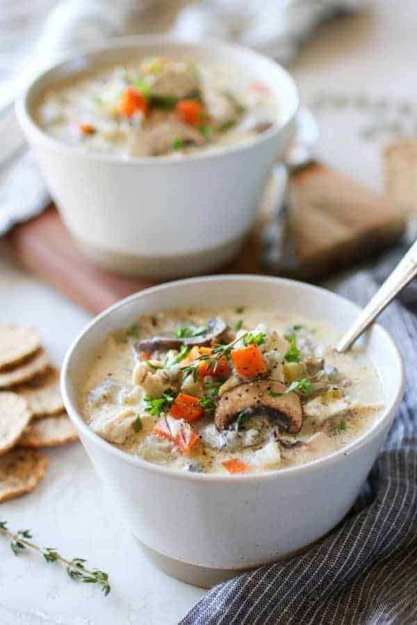 Photo of two white bowls of Slow Cooker Creamy Chicken Wild Rice Soup.