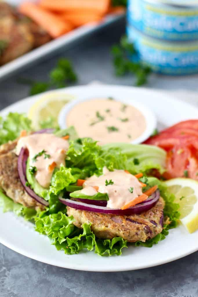 Tuna cakes with onion, lettuce and mayo served on a white plate. Lime and tomato garnish.