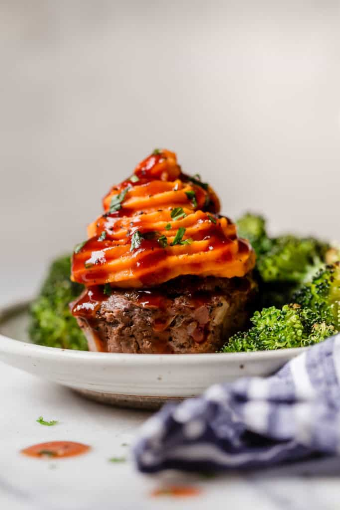 Meatloaf muffin with sweet potato piped on top surrounded with broccoli on a plate