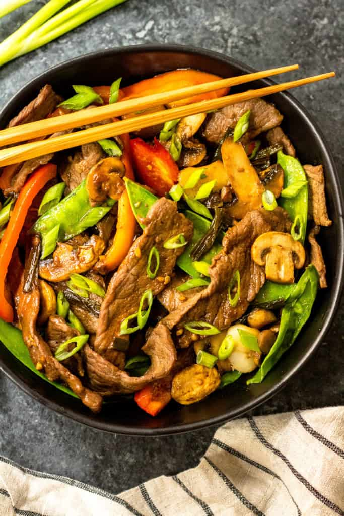 Cast-iron skillet with steak stir fry, mushrooms, peppers and onions with a pair chopsticks resting on top.
