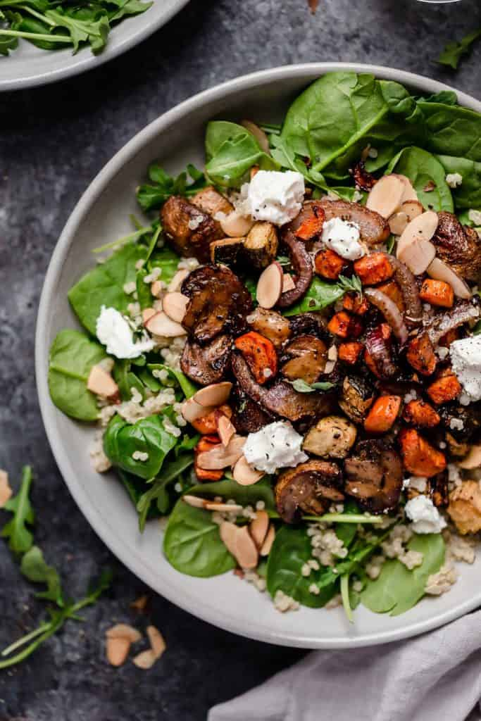 Plate filled with bed of spinach and topped with mushrooms, carrots, almonds and goat cheese