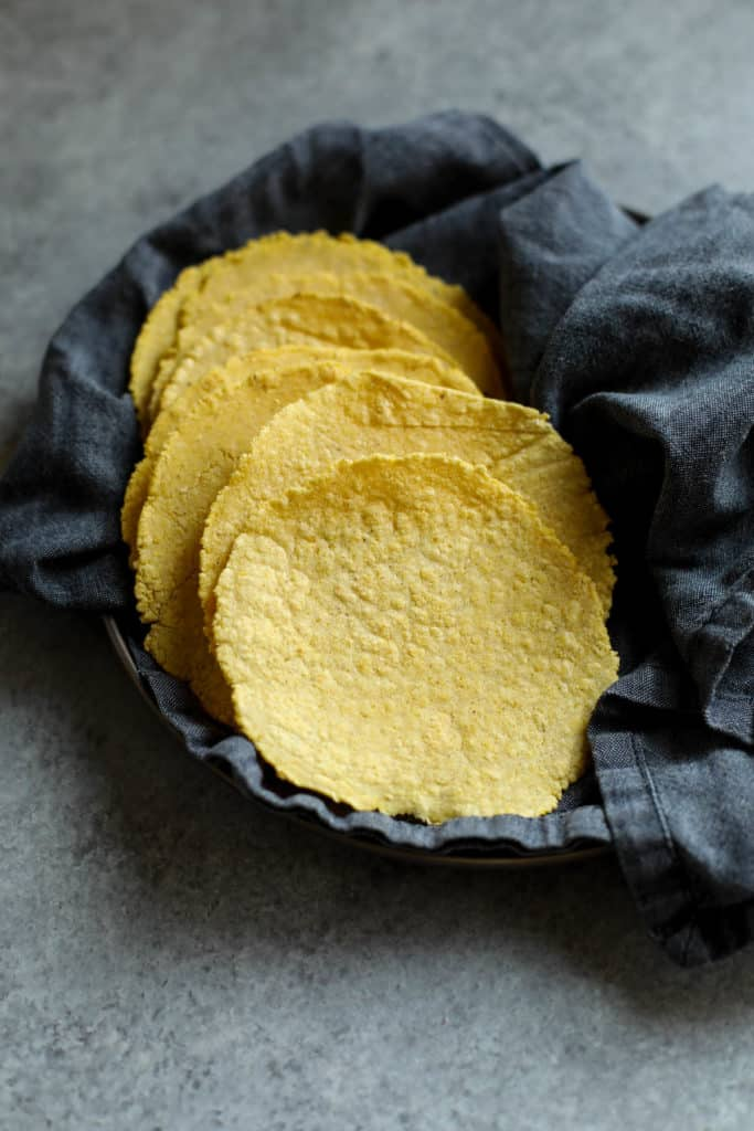 A napkin-lined basket filled with fresh corn tortillas