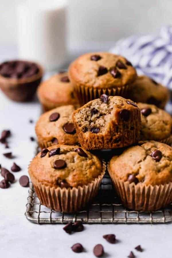 Gluten-free Banana Muffins topped with chocolate chips stacked on top of each other on a metal cooling rack