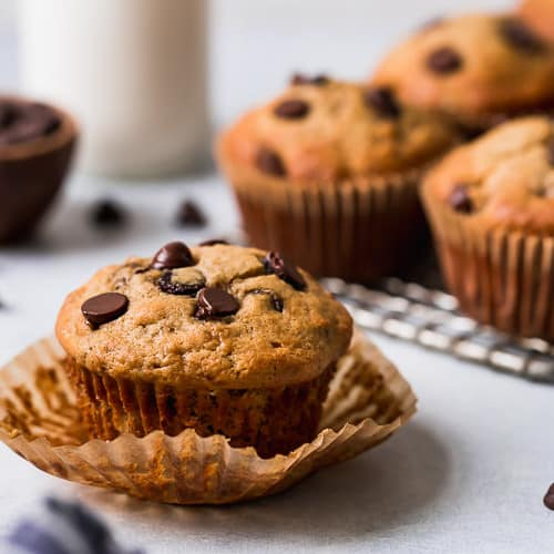 A gluten-free banana muffins topped with chocolate chips on a freshly peeled-away muffin liner.