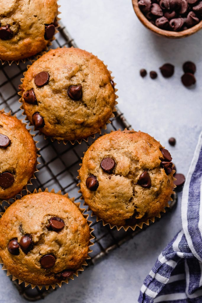 Several banana muffins studded with chocolate chips lined up on a wire cooling rack