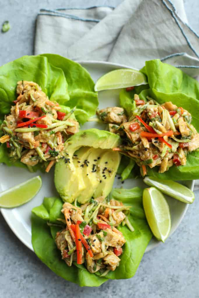 Three lettuce cups on a plate filled with chicken salad containing peppers, broccoli slaw and avocado slices in the middle and lime garnishes