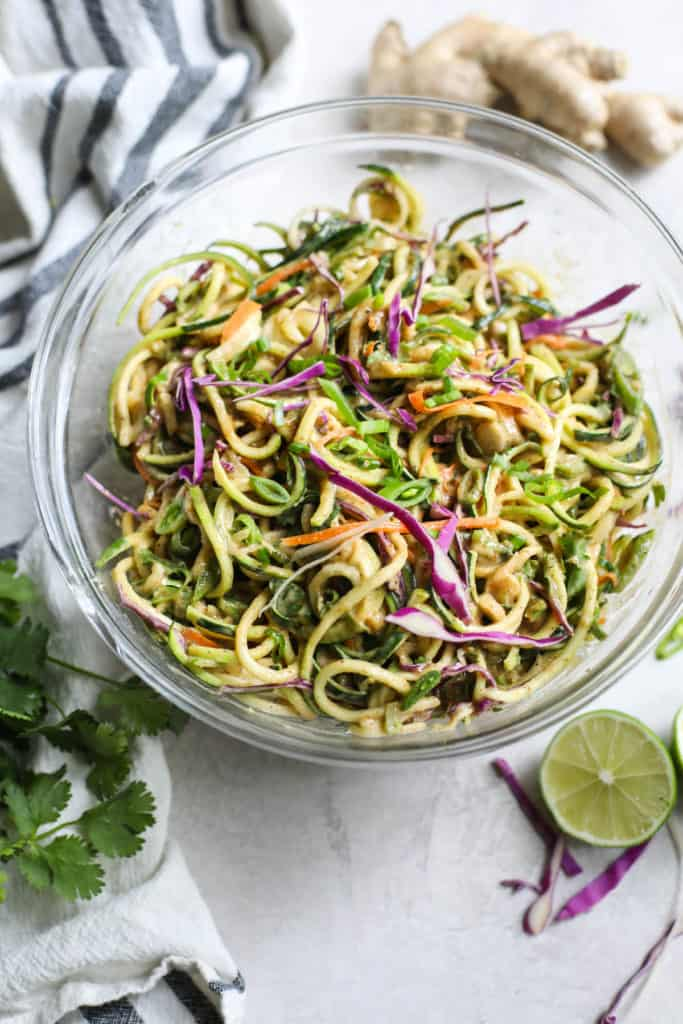 Zucchini noodles with cabbage, carrots, onion in glass bowl surrounded by cilantro, ginger and lime.
