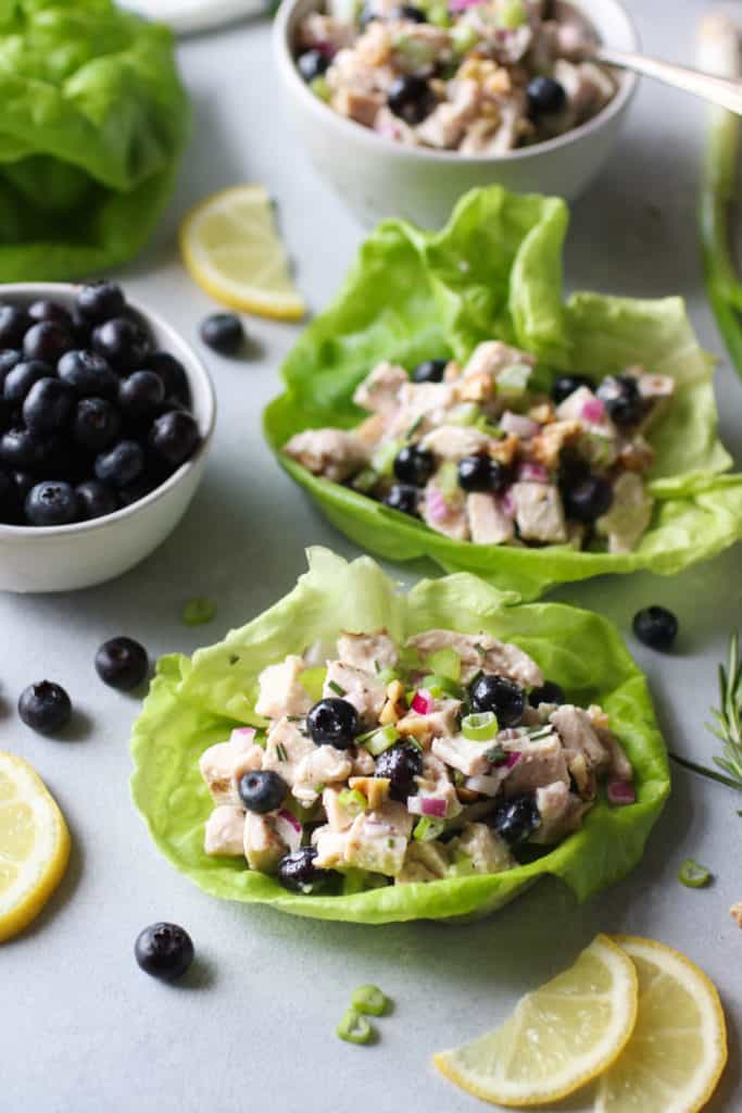 Two lettuce cups filled with chicken salad containing blueberries with blueberries on the side and lemon garnish