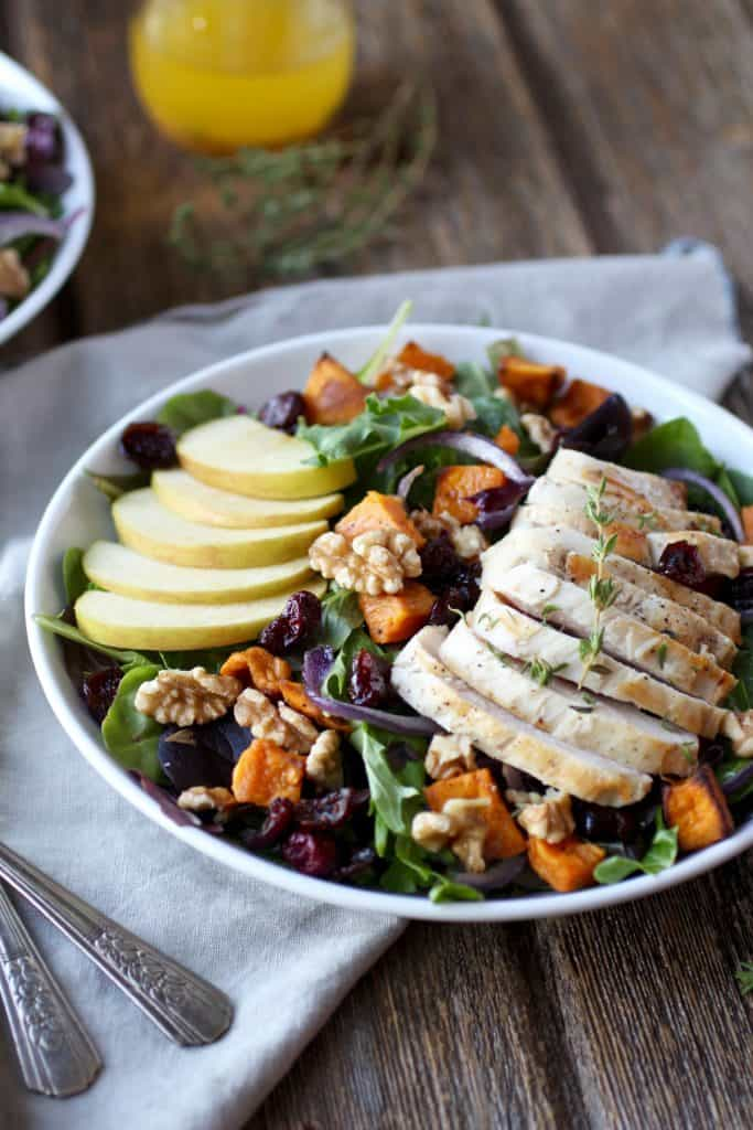 Mixed greens salad topped with apples, walnuts, sweet potato and chicken breast on wooden surface