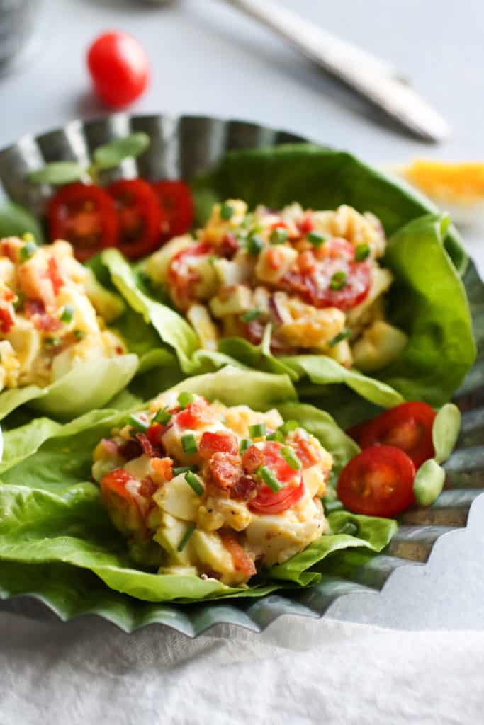 Three lettuce cups filled with egg salad containing tomatoes and bacon on stainless steel tray