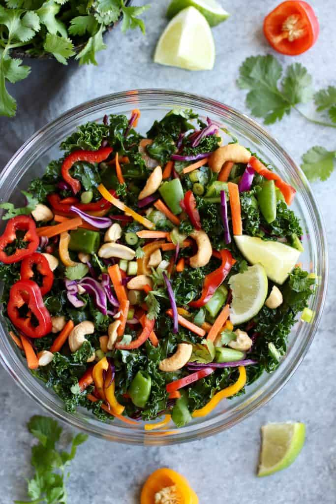 colorful kale salad with peppers, peas and cashews in a glass bowl