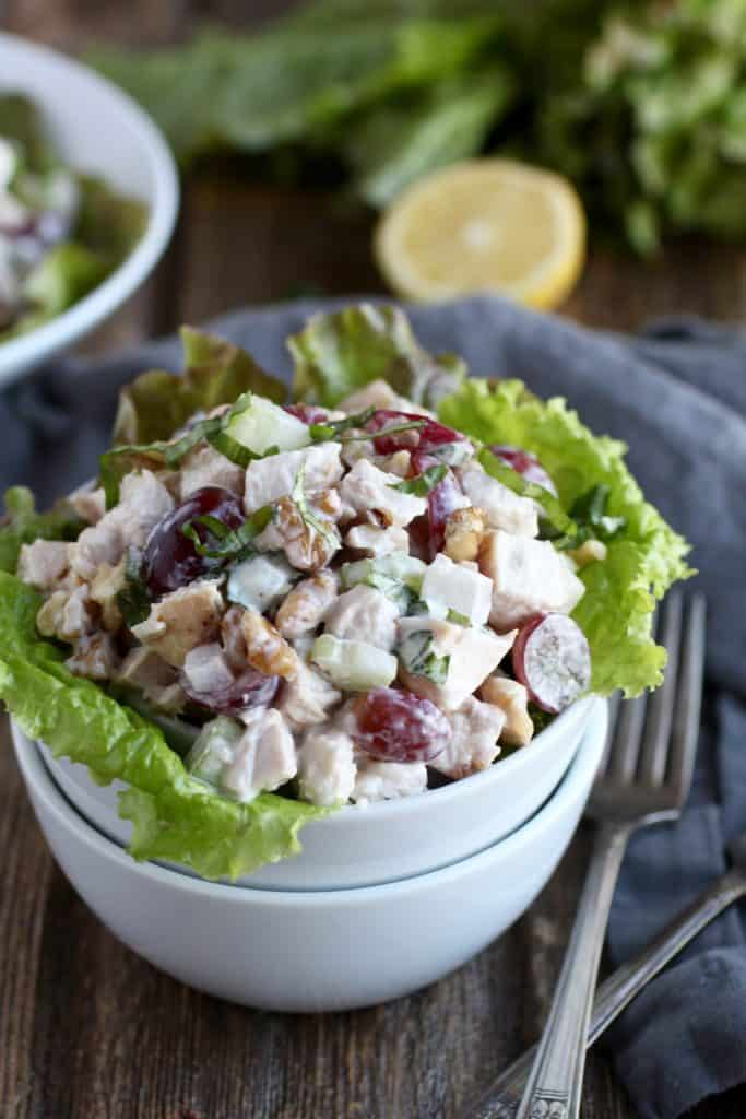 Nested bowls with chicken salad containing walnuts, grapes, celery with lettuce garnish and lemon in the background
