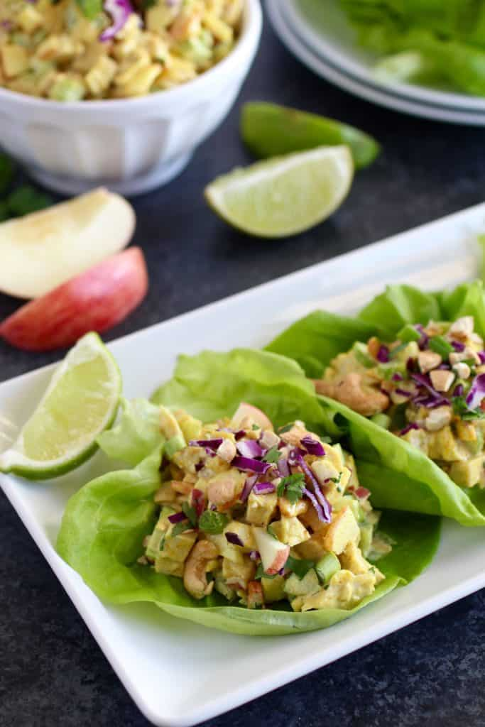 Two lettuce wraps with curry chicken salad on plate topped with apples and cabbage surrounded by apple and lime slices and a bowl of curry chicken salad in the background