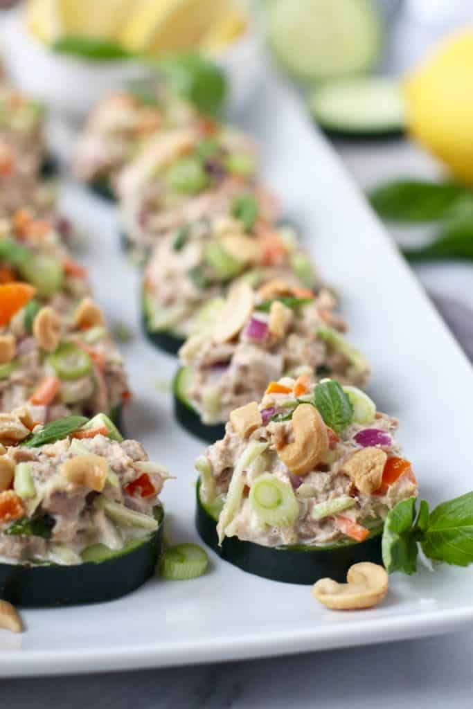 Plate of cucumber slices topped with tuna salad containing onions, cashews, broccoli slaw and peppers