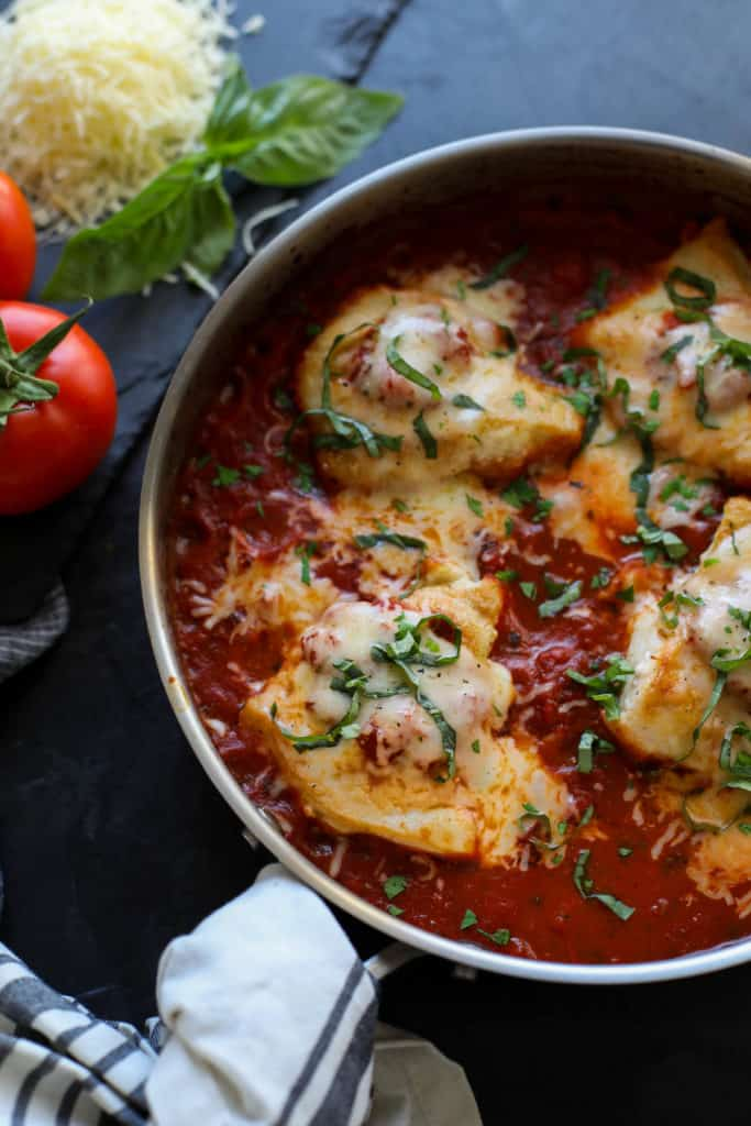 Skillet with tomato sauced and chicken breasts covered in cheese with tomatoes, cheese and basil outside the pan.
