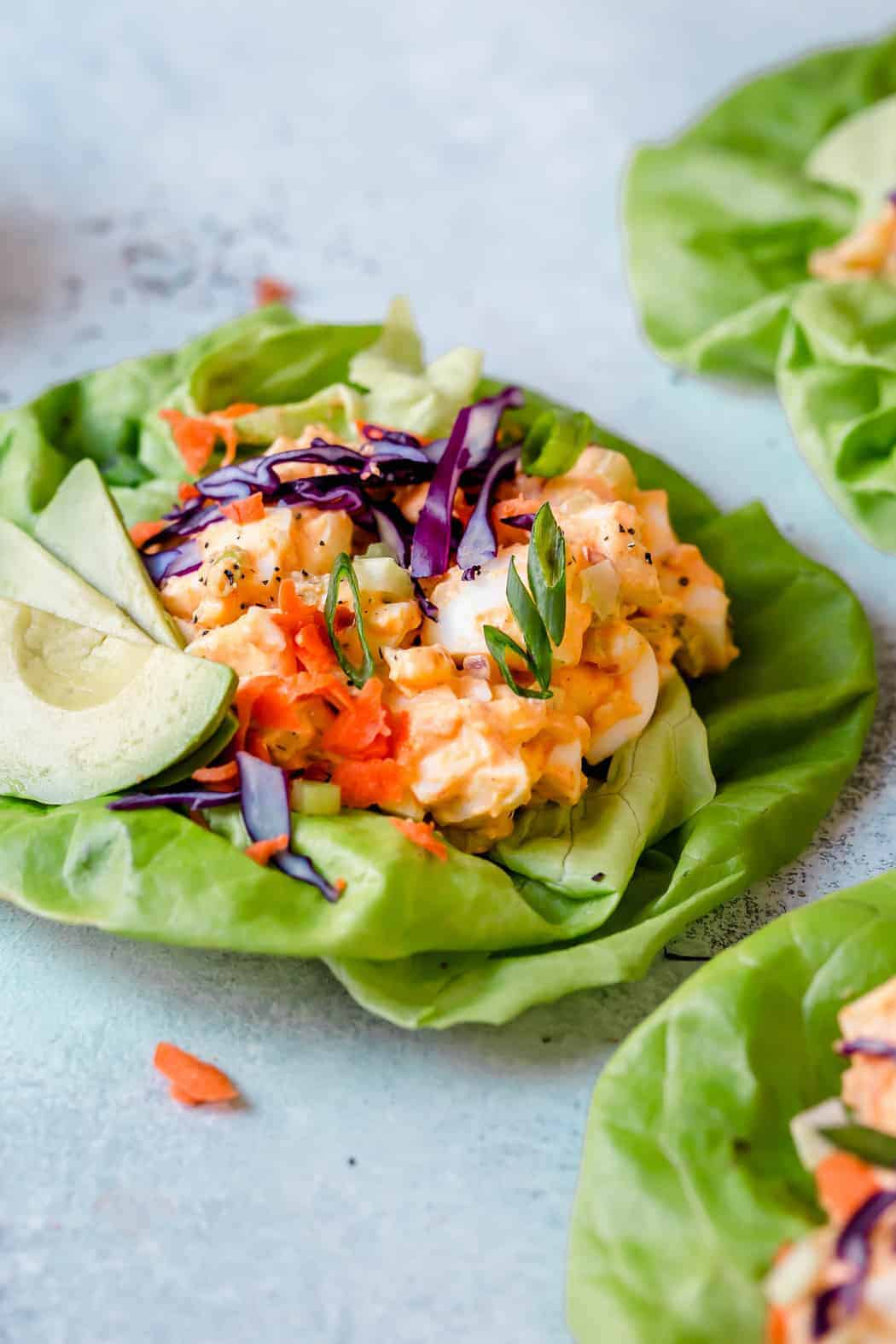 Photo of Buffalo Ranch Egg Salad in a butter lettuce leaf with avocado slice and topped with shredded red cabbage, shredded carrots and green onion slices.