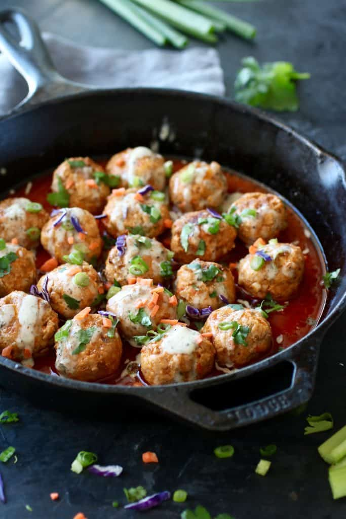 Iron skillet filled with meatballs and surrounded by sauce with veggie accents of purple, green and orange.