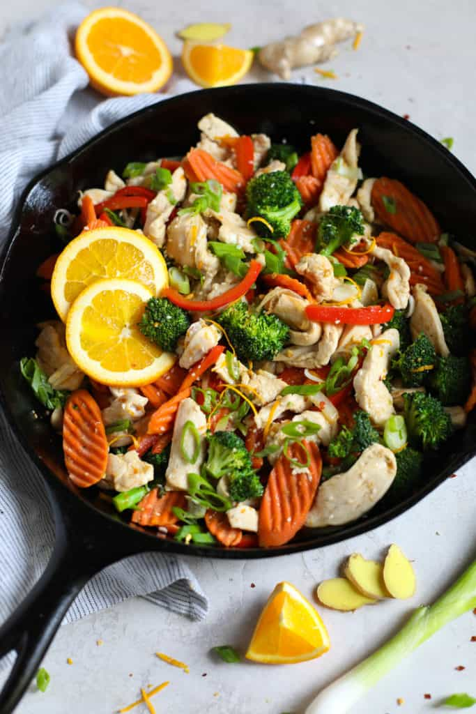 Iron skillet filled with chicken, carrots, broccoli, onions, red peppers and garnished with orange slices