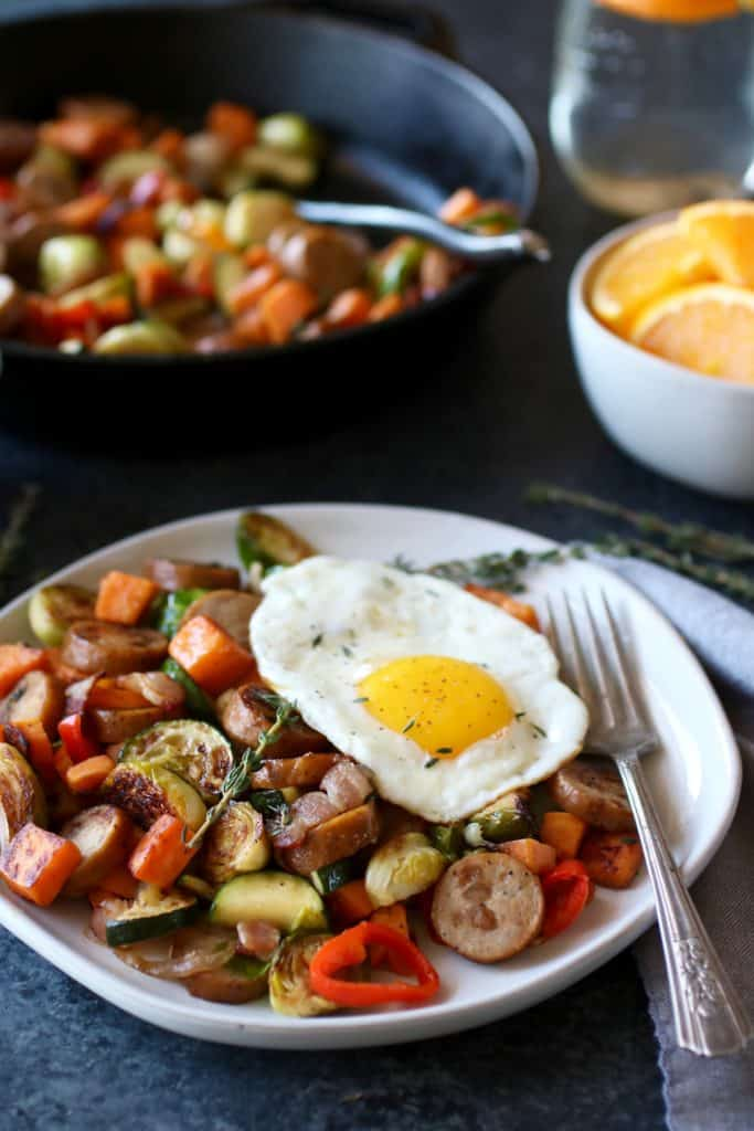 Plate of sliced chicken sausage, zucchini, sweet potato, red peppers, Brussels sprouts topped with an egg with a fork on plate and an iron skillet with more hash in the background as well as a side of orange slices