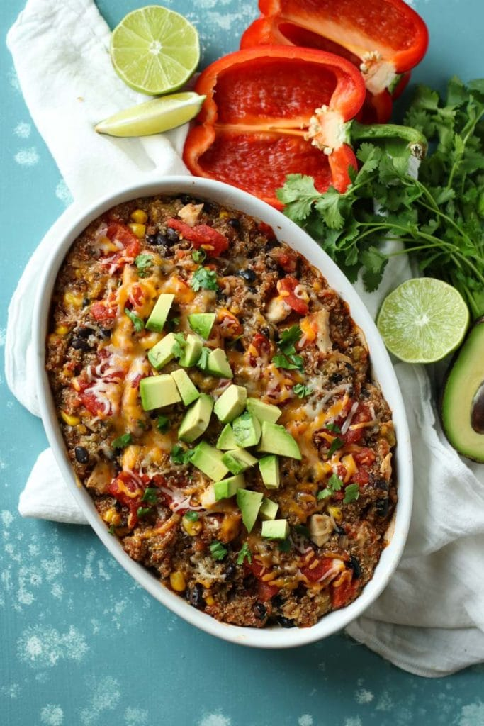 Oval white baking dish with quinoa bake topped with avocado and surrounded by limes, red peppers, limes and cilantro.