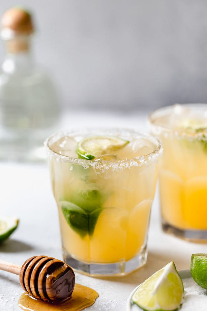 Two margaritas on the rocks with salted rims, honey wand with a pool of honey around it, bottle of tequila in the background with lime garnish
