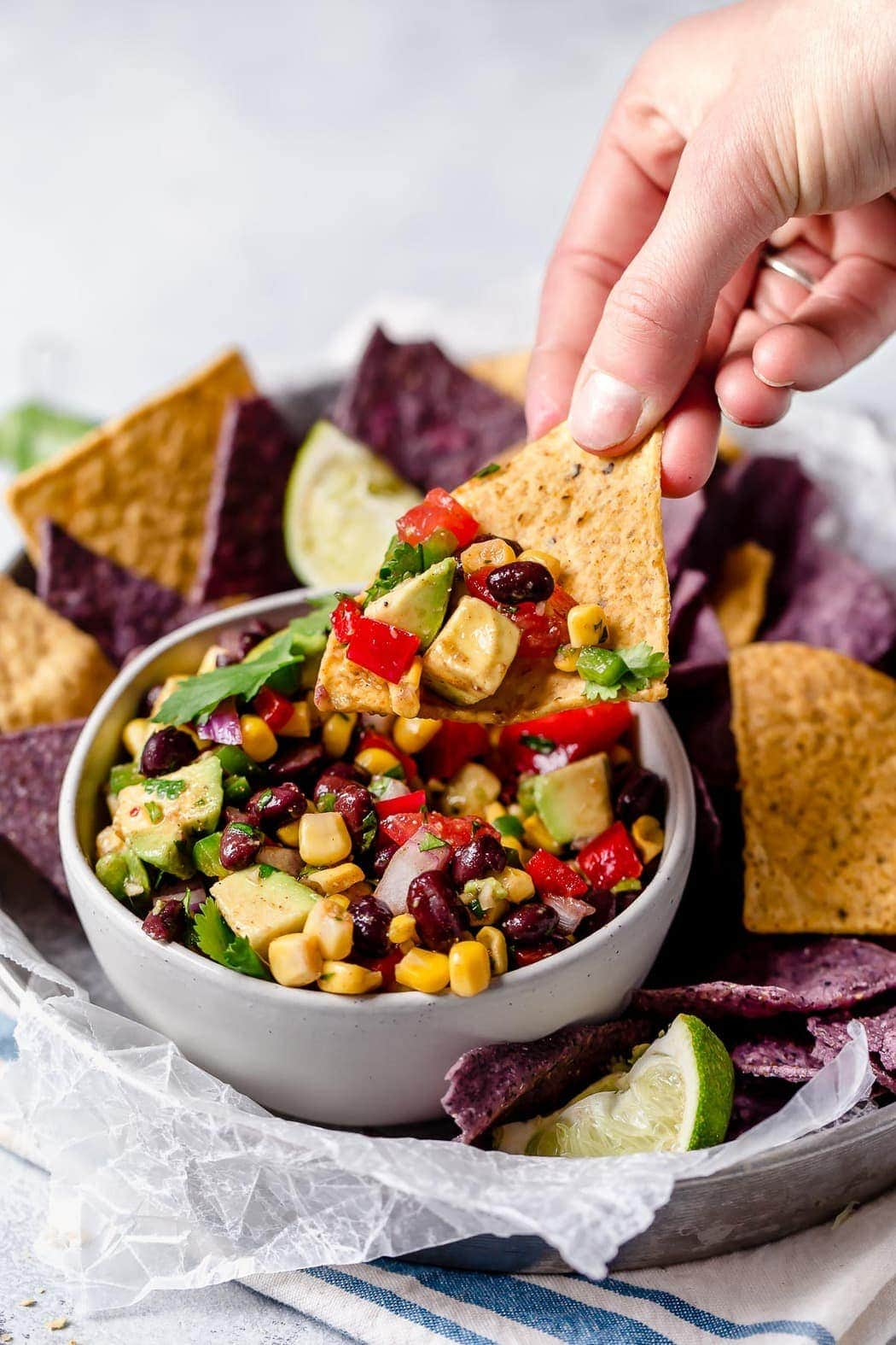 Photo of Black Bean & Corn Salsa with Avocado in a white bowl surrounded by blue and white corn tortilla chips. Showing a hand picking up a chip with a scoop of salsa on it.