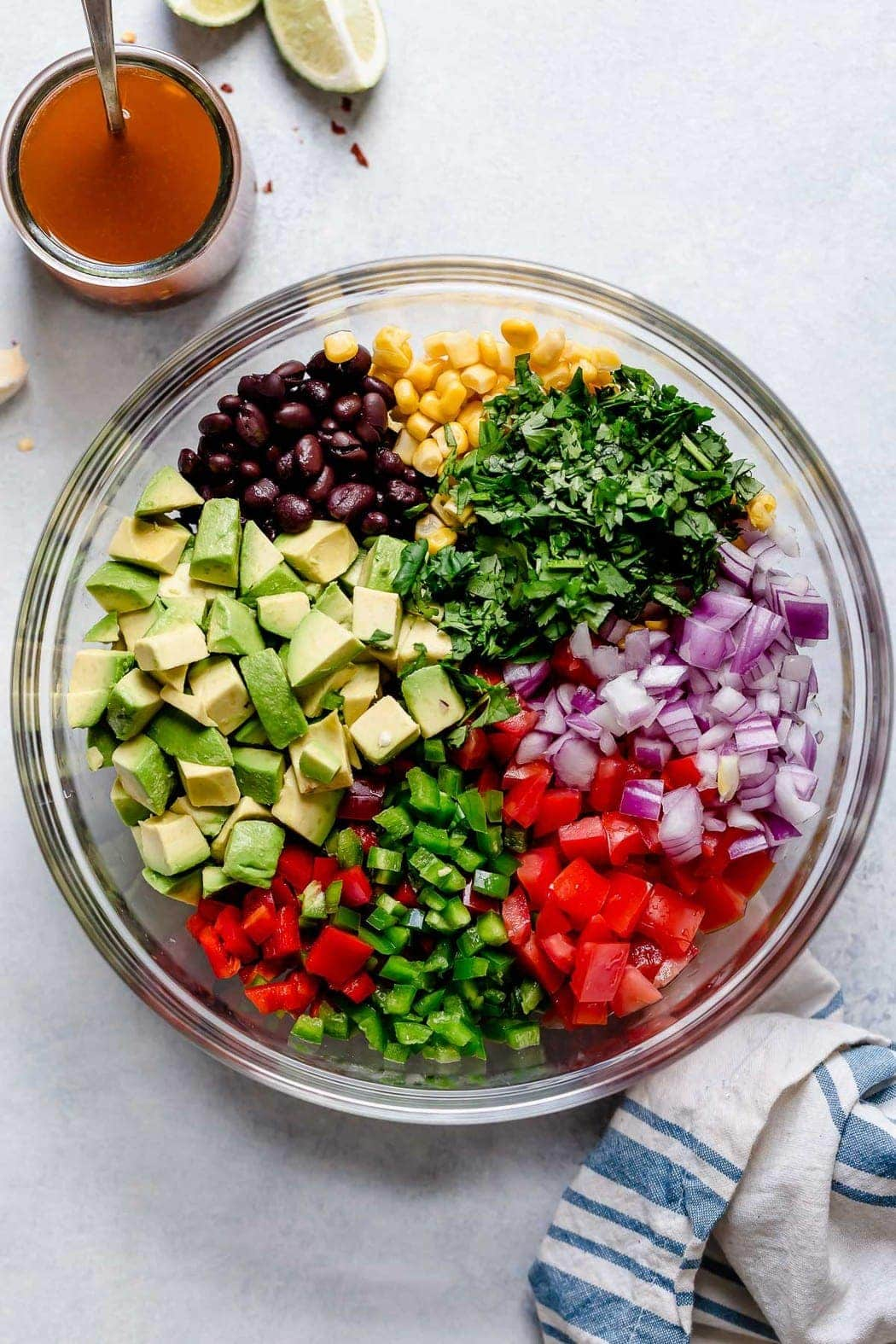 Photo of Black Bean & Corn Salsa with Avocado ingredients in a clear bowl before it has been mixed.