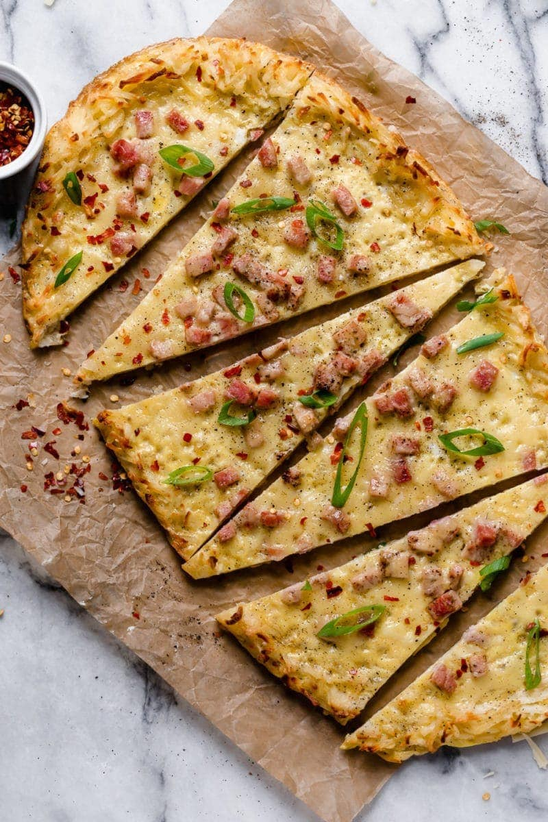 Overhead photo of Breakfast Pizza with Hash Brown Crust topped with green onion slices and crushed red pepper. Sliced into 6 triangles.