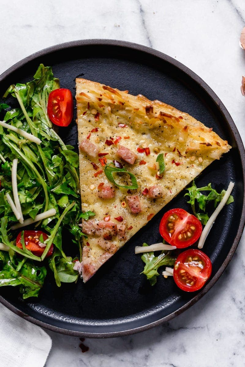 Overhead photo of a slice of Breakfast Pizza with Hash Brown Crust on a black plate topped with green onion slices and crushed red pepper. Also served on the plate is a green salad with cherry tomatoes halves.