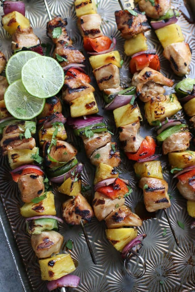 Chicken kebabs with peppers, pineapple, and onions with lime slice garnish on baking sheet.