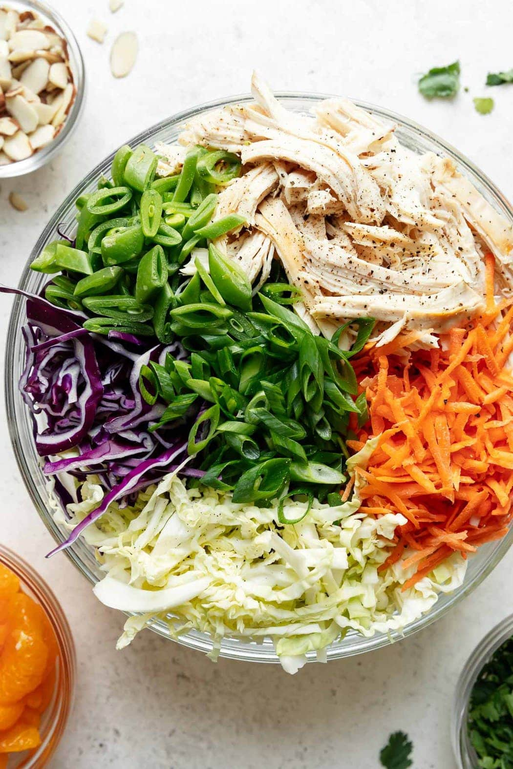 All ingredients for Chinese chicken salad in a large bowl ready to be toss together