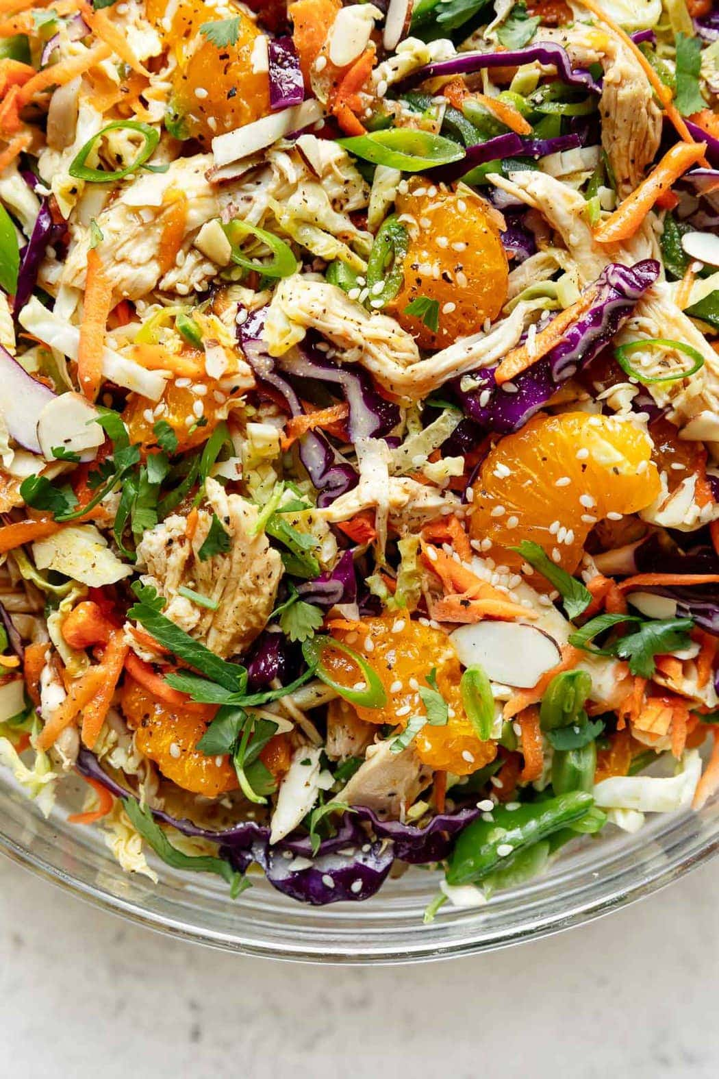 A close up view of Chinese-inspired chicken salad with shredded chicken, shredded cabbage, snap peas, and toasted almonds in a serving bowl