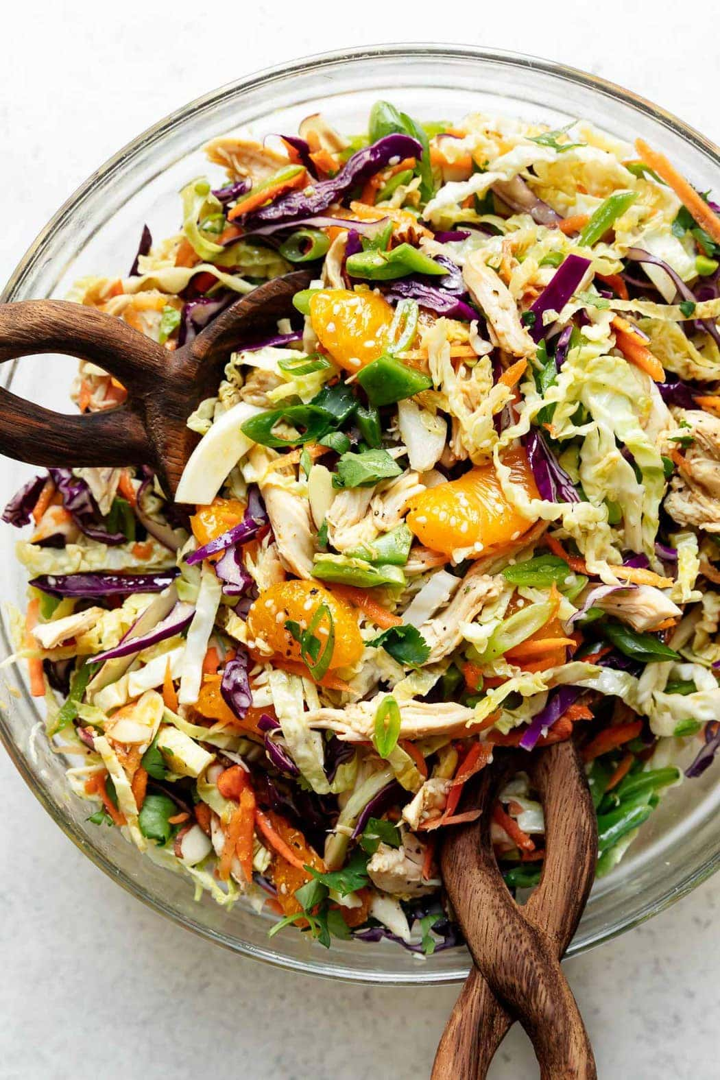 A large serving bowl filled with mandarin orange chicken salad with two wooden handled salad spoons in the salad
