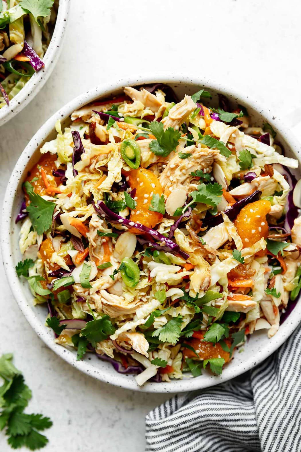 A big bowl of Chinese chicken salad topped with fresh herbs, purple cabbage, and mandarin oranges