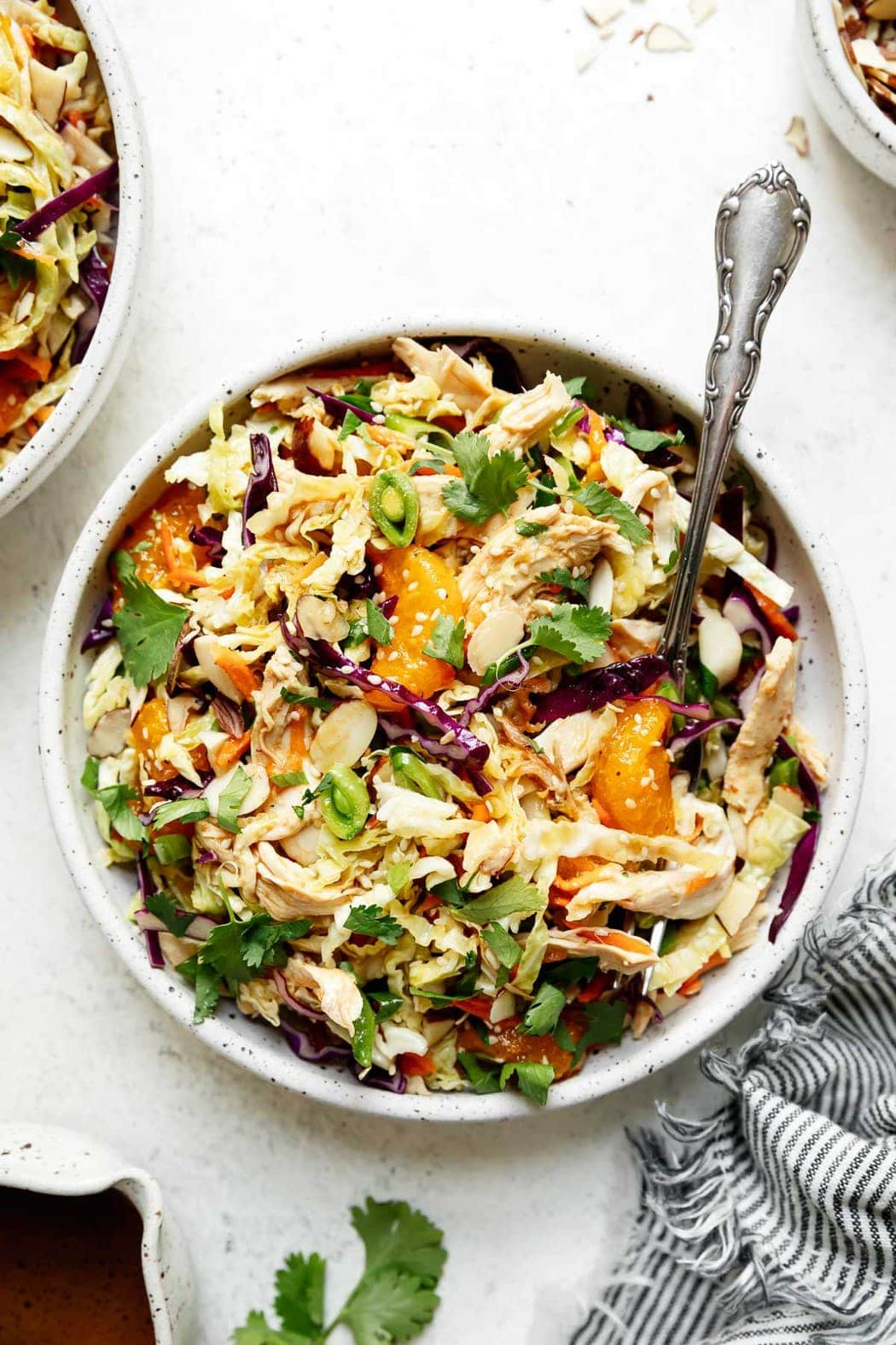 A large bowl filled with Chinese chicken salad topped with sliced snap peas, purple cabbage shreds, sesame seeds, and orange slices.