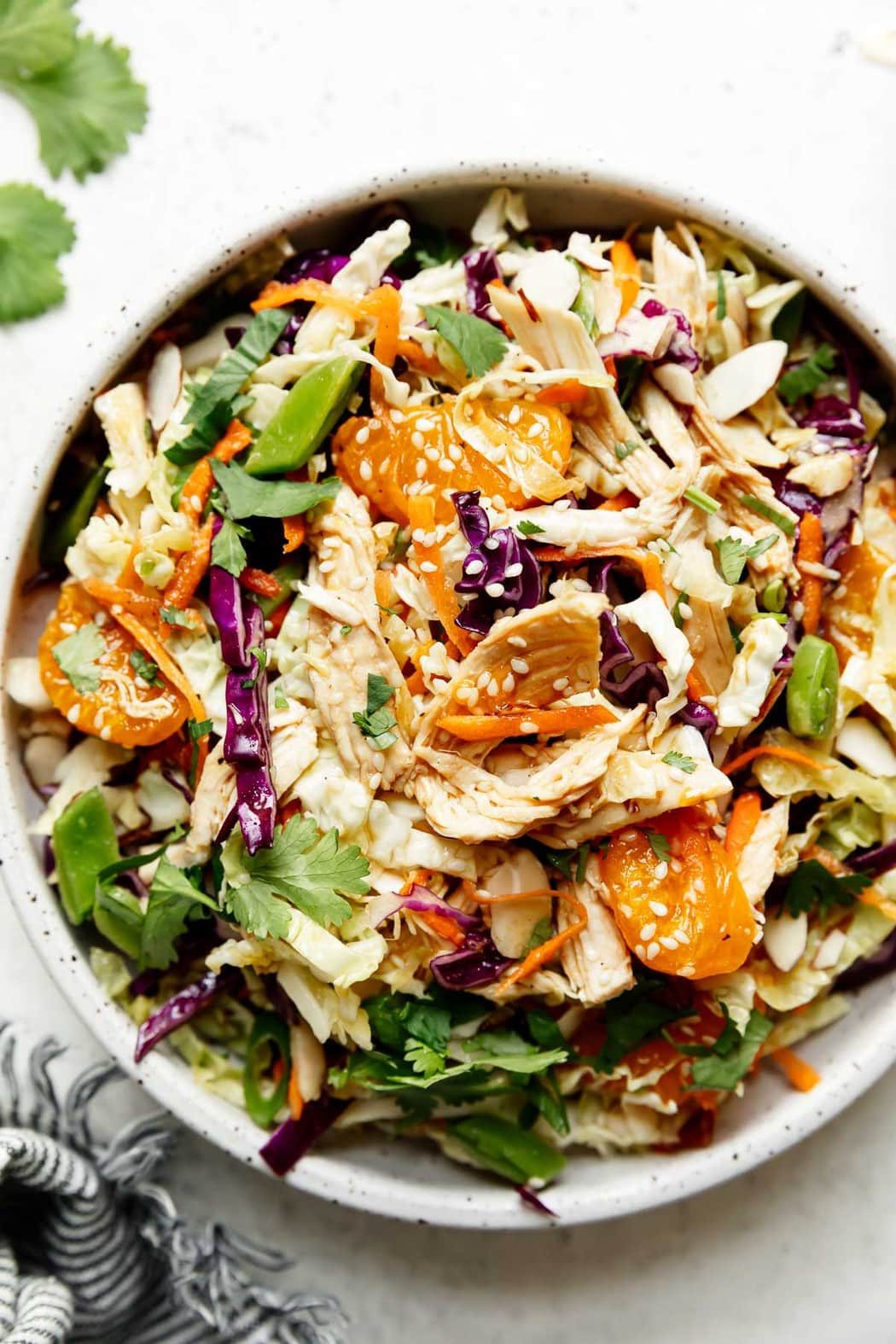 Overhead view of Chinese chicken salad topped with chicken, sesame seeds, purple cabbage, and mandarin oranges.