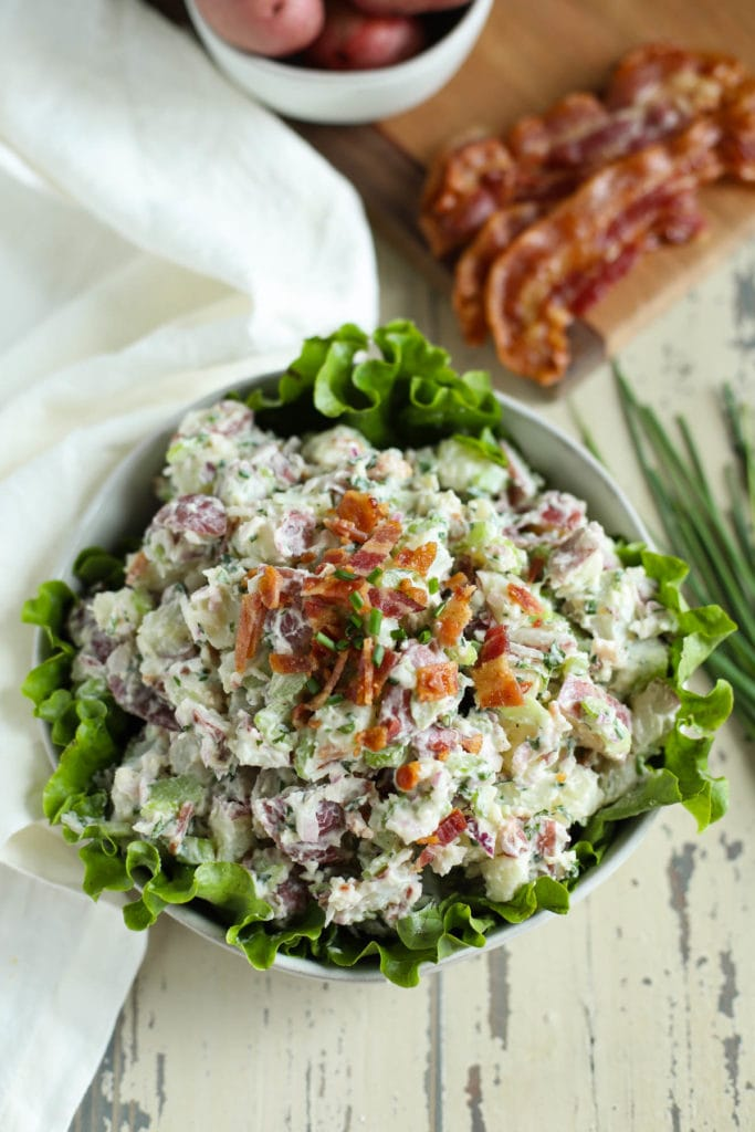 Lettuce-lined bowl filled with potato salad with bacon crumbled on top with potatoes and bacon in background on weathered white surface.