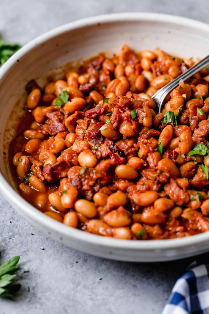 Bowl of baked beans with bacon with a spoon scooping some out with green garnish