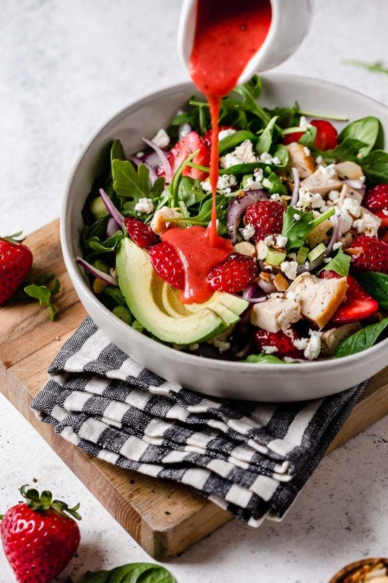 Photo of red dressing being drizzled on the Strawberry Spinach Salad with Chicken in a white bowl. Ingredients include greens, sliced strawberries, chunks of chicken, goat cheese crumbles, avocado slices and red onion slices.