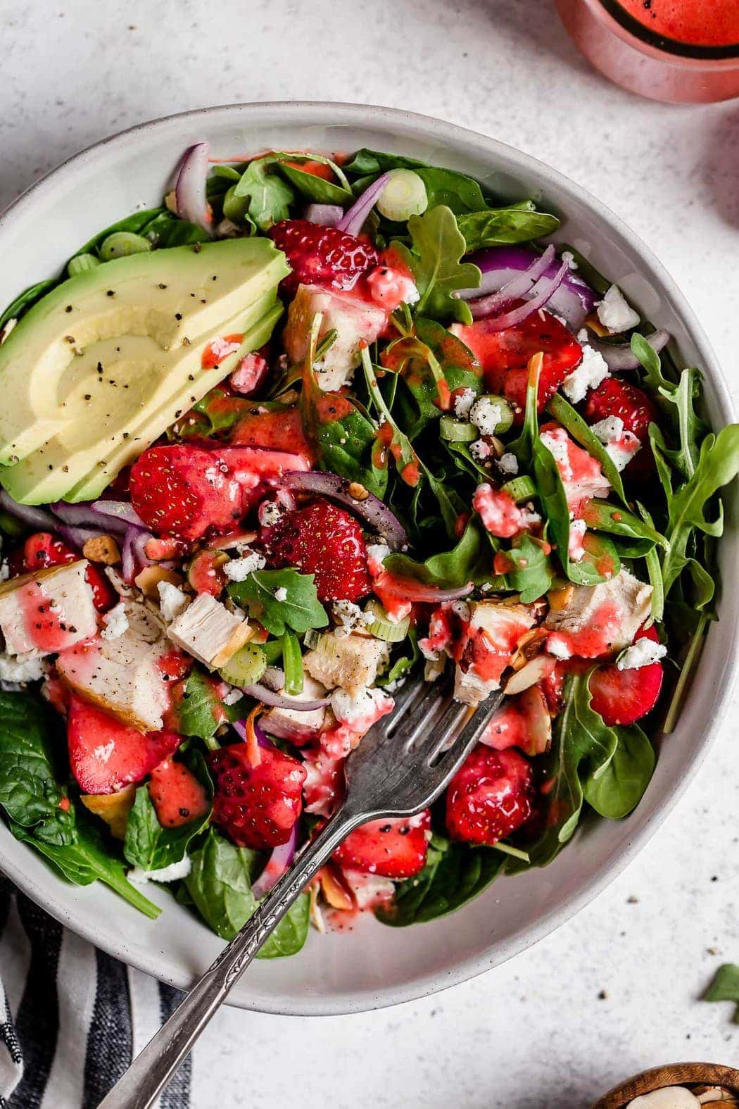 Gorgeous overhead shot of Strawberry Spinach Salad with Chicken in a white bowl. Ingredients include greens, sliced strawberries, chunks of chicken, goat cheese crumbles, avocado slices and red onion slices.