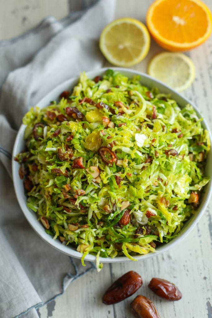 Shredded Brussels slaw in a bowl with citrus garnish